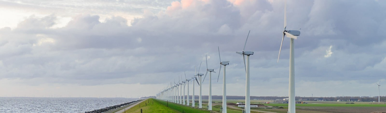 A row of environmentally sustainable windmills on a cloudy day