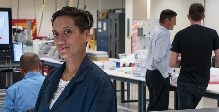 A woman stands apart from her peers in a medical device lab